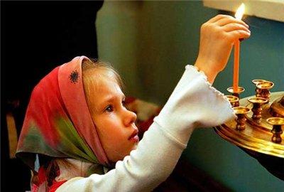 Девочка зажигает свечу в храме